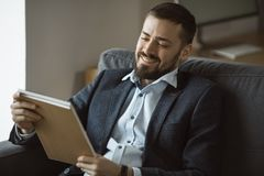 Man Working In Office Doing Notes. Working with pleasure. Handsome young man in glasses making some notes in his note pad with smile while sitting at his working royalty free stock photography