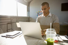 Man working in office on sunny day. Young man using laptop at desk in office on sunny day stock photos