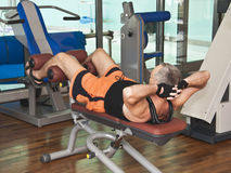 Man working out abdominal in gym Stock Photos