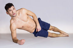 Man working out abs. Handsome man working out exercises on a white background Royalty Free Stock Photos