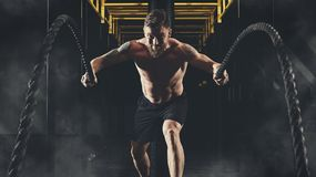 Man working out with battle ropes at gym Royalty Free Stock Photo