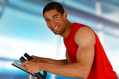 Man Working Out On Bike. Man working out while at the gym on bike Stock Photo