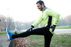 Man working out in the city park. And stretching muscles Stock Photos