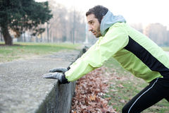 Man working out in the city park. And stretching muscles Stock Image