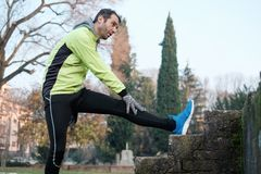 Man working out in the city park and stretching. Muscles Royalty Free Stock Images