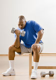 Man working out with dumbbells in health club. Determined man working out with dumbbells in health club Royalty Free Stock Photos