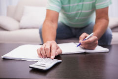 Man working out his finances on the couch Royalty Free Stock Photos