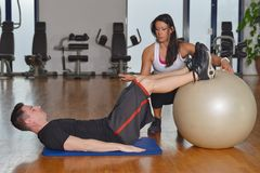 Man working out with his pesonal trainer. Man working out while female personal instructor assisting him Royalty Free Stock Photo