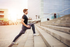Man working out. A photo of young, muscular man training on the city stairs Royalty Free Stock Images