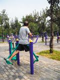 Man working out on public equipment in the park stock images