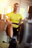 Man working out on row machine in fitness studio Royalty Free Stock Photography