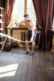 Man working out with training ropes at home. Royalty Free Stock Photos