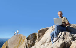 Man working outdoor. With 2 seagulls watching Royalty Free Stock Photography