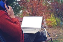 Man working outdoors always connected with his smartphone and his loyal laptop. young guy, freelancer working outdoors royalty free stock photo