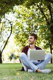 Handsome young man using laptop outdoors. Man working outdoors on laptop. Preparing for exams, sitting on grass at university campus park. Technology Royalty Free Stock Images
