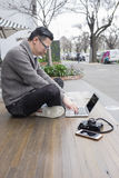 Man working outdoors. Man sitting and working on laptop outdoors, and camera and phone beside stock photography