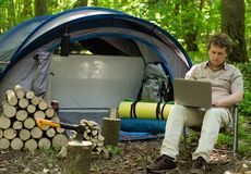 Man Working Outdoors In A Tent Camp. Stock Image
