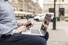 Man working outside office with phone in hand, focus on the phone Stock Photos