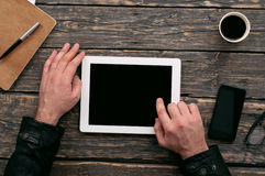 Man working outside the office with a tablet computer. On a dark wooden table in a cafe, top view Royalty Free Stock Image