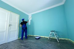 Man in a working overall. Is painting the wall in white color stock images