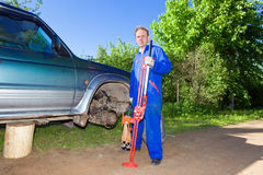 The man in working overalls changes a wheel Royalty Free Stock Photos