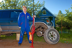 The man in working overalls replaces a wheel Royalty Free Stock Image