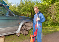 The man in working overalls replaces a wheel at an off-road car Royalty Free Stock Photo