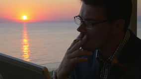 Man working with pad on the balcony at sunset. Slow motion of a young businessman using tablet PC and smoking while sitting at the balcony with view to the sea stock video