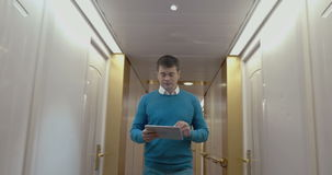 Man working with pad in hotel hallway stock video footage