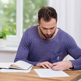 Man working on paperwork at home Stock Photography