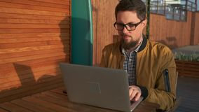Man working on pc outside. Young bearded man sitting outside connected to cafe`s wifi. Freelancer working on laptop in the evening. Thoughtful and focused guy stock video