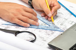 Man working with pencil and a magnifier on blueprints Royalty Free Stock Photography