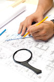 Man working with pencil and a square drawing on blueprints Royalty Free Stock Photos