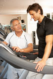 Man Working With Personal Trainer. On Running Machine In Gym Royalty Free Stock Photography