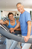 Man Working With Personal Trainer. On Running Machine In Gym Stock Photography