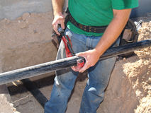 Man Working on Pipe - Horizontal Stock Photo