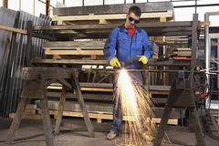 Man working with plasma cutter. On steel plate at industrial workshop royalty free stock photography