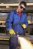 Man working with plasma cutter. On steel plate at industrial workshop stock photos