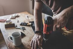 Man working with power drill. Man drilling laminate with power drill on the table Royalty Free Stock Image