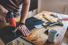 Man working with power drill. Man drilling laminate with power drill on the table Royalty Free Stock Images