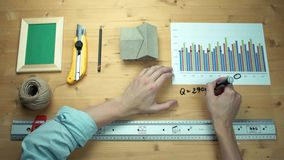 Man working with printed graphs making notes with marker at wooden desk. Ruler, house model, realistic mockup wooden photo frame, yellow paper knife, craft stock video
