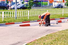 Man working. Repaints with a brush the road concrete limiter in road coloring. royalty free stock image