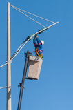 Man working replacing bulb of a lamp post. Stock Image