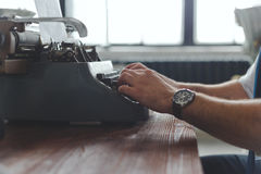 Man working on retro typewriter at desk in parlor room Royalty Free Stock Image