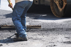 Man working on road construction site. Man working on paving the road Stock Photos