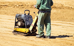 Man is working at the road construction. With a soil compactor machinery Stock Image
