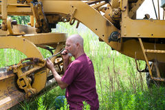 Man working on road equipment Stock Image