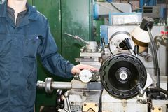 A man working in a robe, overalls stands next to an industrial lathe for cutting, turning knives from metals, wood other materials stock photography