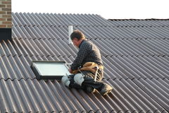 Man working on roof. Man sitting on roof working on skylight Stock Photos