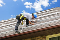 Man working on roof installing solar panels stock image